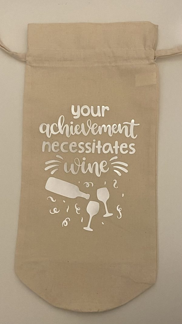 """Handmade wine bag with the words """"Your achievement necessitates wine"""" in silver, two glasses below the words with a bottle pouring above the glasses."""